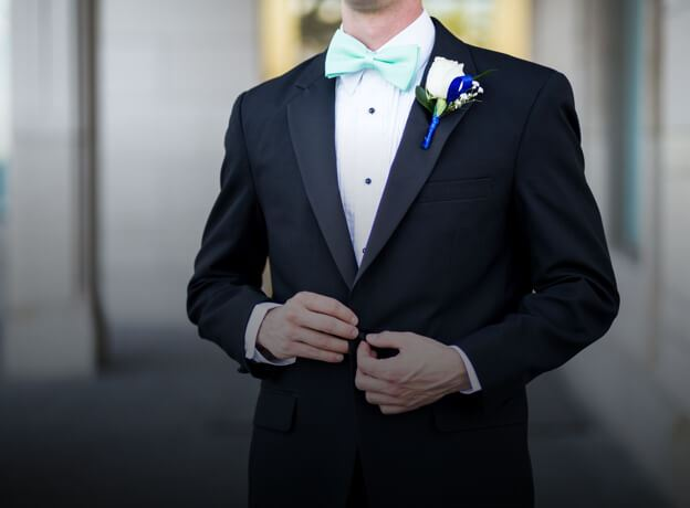 Male model wearing black tuxedo and mint blue bow tie shown on mobile device